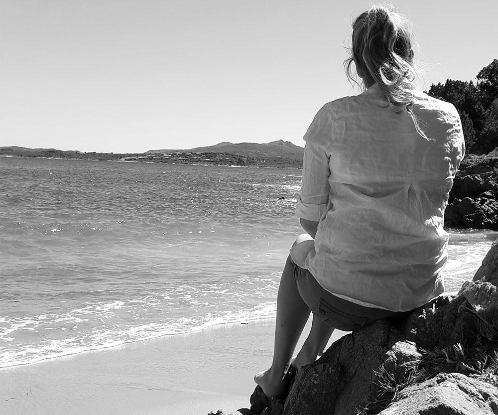 redakteurina sitzt auf einem Felsen und blickt auf das Meer