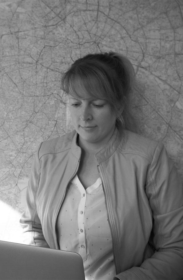 redakteurina sitzt am Laptop und schreibt. Im Hintergrund ist eine Berlinkarte zu sehen.